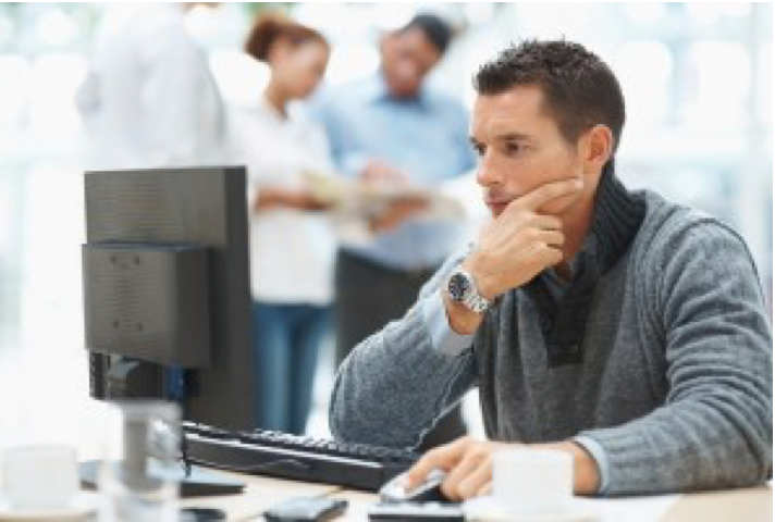 man working on staring at computer screen while working