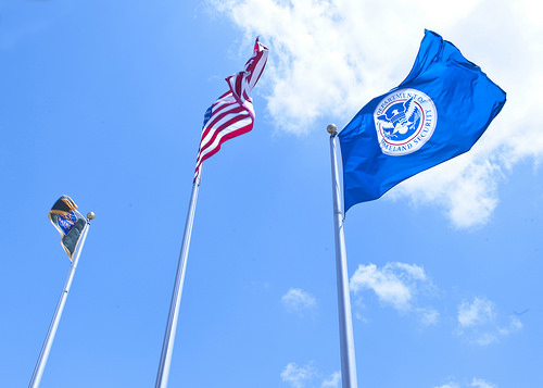 There flags flying in the wind including the United States and the Department of Homeland Security