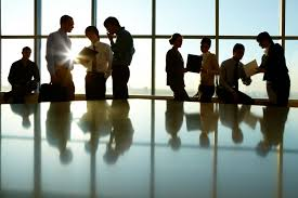 group of people standing in an office conference room