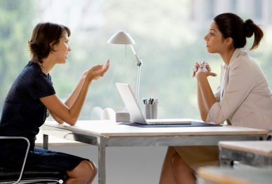image of two working women discussing business at a desk