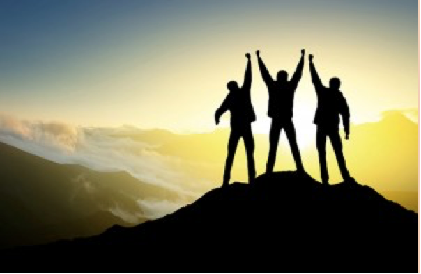 three people at the top of a mountain with their arms up in achievement