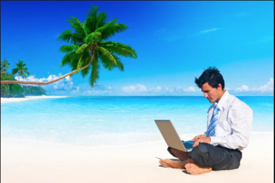 man in a suit and tie sit-in barefoot on the beach with his laptop