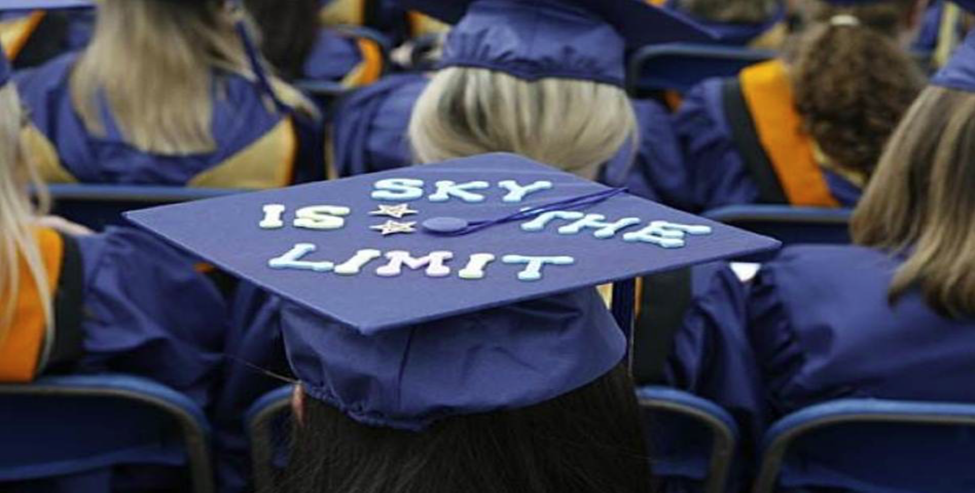 sky is the limit graudation hat viewed within a crowd of graduates